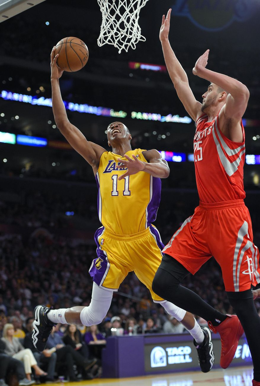 Los Angeles Lakers forward Wesley Johnson shoots as Houston Rockets forward Chandler Parsons defends during the first half of an NBA basketball game, Tuesday, April 8, 2014, in Los Angeles. (AP Photo/Mark J. Terrill)
