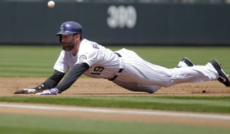 Colorado Rockies right fielder Charlie Blackmon slides into third after hitting triple off of Chicago White Sox' Erik Johnson during the first inning of a baseball game, Wednesday, April 9, 2014, in Denver. (AP Photo/Barry Gutierrez)