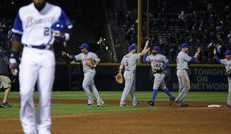 New York Mets players high-five each other as Atlanta Braves' Jason Heyward, left, walks off the field after flying out in the ninth inning to end a baseball game, Tuesday, April 8, 2014, in Atlanta. New York won 4-0. (AP Photo/David Goldman)