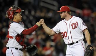 Washington Nationals relief pitcher Aaron Barrett (30) celebrates 5-0 win over the Miami Marlins with catcher Jose Lobaton, left, during the inning of a baseball game, Tuesday, April 8, 2014, in Washington. (AP Photo/Nick Wass) **FILE**