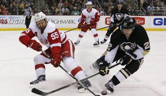 Detroit Red Wings' Niklas Kronwall (55) clears the puck before Pittsburgh Penguins' Lee Stempniak (22) can get his stick on it during the second period of an NHL hockey game in Pittsburgh, Wednesday, April 9, 2014. (AP Photo/Gene J. Puskar)