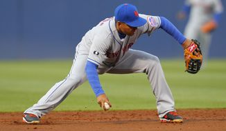 New York Mets shortstop Ruben Tejada bobbles the ball but throws to second for the force-out in the first inning of the baseball game against the Atlanta Braves, Wednesday, April 9, 2014, in Atlanta. (AP Photo/Todd Kirkland)