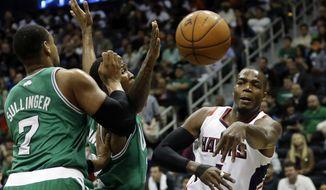 Atlanta Hawks' Paul Millsap, right, passes the ball past Boston Celtics' Jared Sullinger, left, and Chris Johnson in the second quarter of an NBA basketball game, Wednesday, April 9, 2014, in Atlanta. (AP Photo/David Goldman)