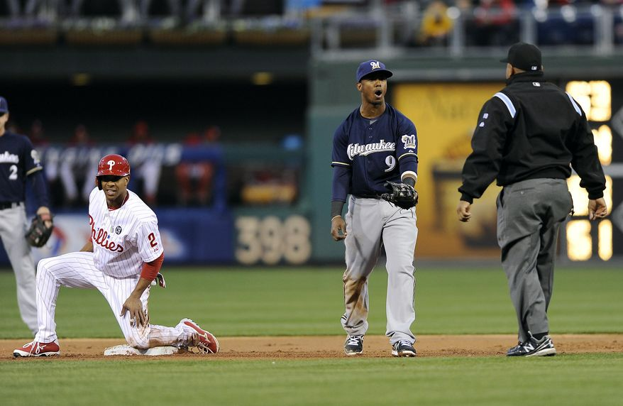 Milwaukee Brewers shortstop Jean Segura (9) argues a call with umpire Adrian Johnson, right, as Philadelphia Phillies'  Ben Revere looks on from second base during the first inning of a baseball game on Wednesday, April 9, 2014, in Philadelphia. (AP Photo/Michael Perez)