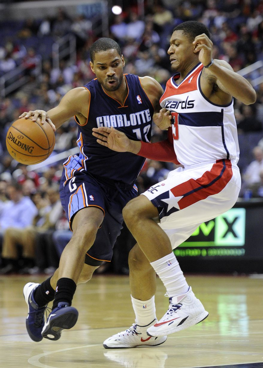 Charlotte Bobcats guard Gary Neal (12) drives to the basket against Washington Wizards guard Bradley Beal (3) during the first half of an NBA basketball game on Wednesday, April 9, 2014, in Washington. Neal was charged with a foul on the play. (AP Photo/Nick Wass)
