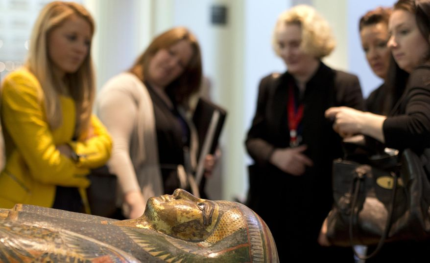 Members of the media stand around the Mummy of Tamut, a temple singer around 900 BC, during a press conference at the British Museum in London, Wednesday April 9, 2014. Scientists at the British Museum have used CT scans and volume graphics software to go beneath the bandages, revealing the skin, bones, internal organs, and in one case a brain-scooping rod left inside a skull by embalmers. The results are going on display in an exhibition which sets eight of the museum's mummies alongside detailed 3-D images of their insides. (AP Photo/Alastair Grant)