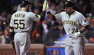 Pittsburgh Pirates' Pedro Alvarez (24), celebrates with Russell Martin (55) at home plate after hitting a solo home run during the fifth inning of a baseball game against the Chicago Cubs in Chicago, Wednesday, April 9, 2014. (AP Photo/Paul Beaty)