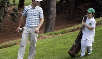Zach Johnson walks with his son Will during the par three competition at the Masters golf tournament Wednesday, April 9, 2014, in Augusta, Ga. (AP Photo/Darron Cummings)