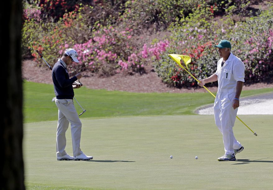 Adam Scott, of Australia, takes notes on the 13th green with caddie Steve Williams during a practice round for the Masters golf tournament Wednesday, April 9, 2014, in Augusta, Ga. (AP Photo/David J. Phillip)