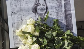 FILE - In this Saturday, April 5, 2014 file photo, roses lay in front of a picture of the Associated Press photographer Anja Niedringhaus, 48, who was killed April 4, 2014 in Afghanistan, in Paris.  Fellow officers say the Afghan police commander who killed Niedringhaus and wounded reporter Kathy Gannon seemed a calm, pious man who may have come under the influence of Islamic fundamentalists calling for vengeance against foreigners over drone strikes. (AP Photo/Michel Euler, File)