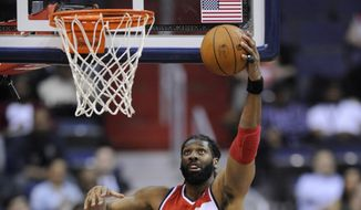 Washington Wizards forward Nene, top, of Brazil, goes to the basket against Charlotte Bobcats guard Luke Ridnour (13) during the first half of an NBA basketball game on Wednesday, April 9, 2014, in Washington. (AP Photo/Nick Wass)