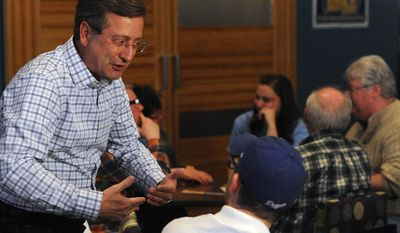In this Tuesday, April 8, 2014 photo, Sioux Falls Mayor Mike Huether talks with a supporter at a hotel in downtown Sioux Falls, S.D.  The mayor of South Dakota's largest city will serve another four years in office after he beat challenger Greg Jamison in Tuesday's election. (AP Photo/The Argus Leader, Jay Pickthorn) NO SALES