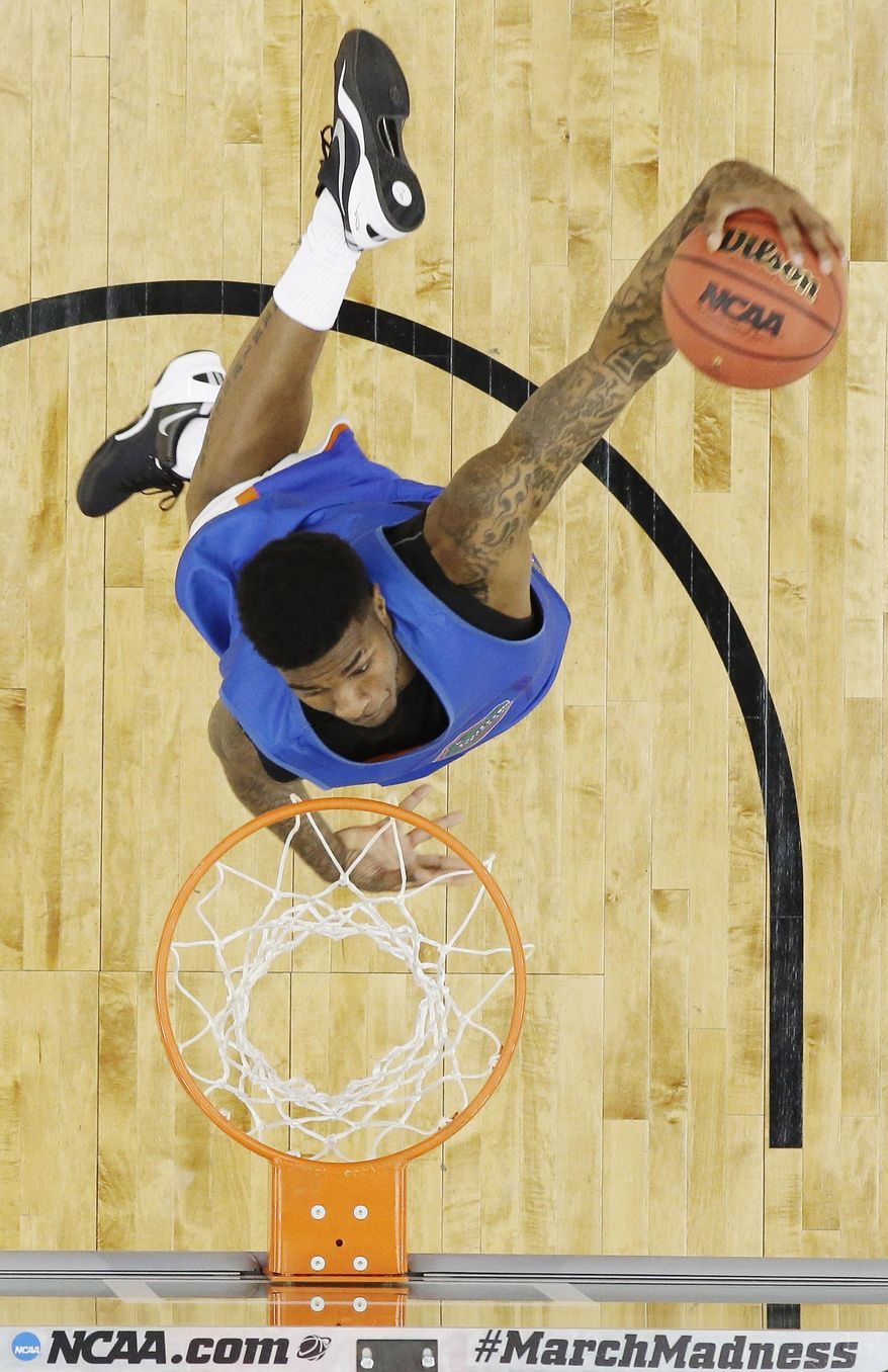 Florida forward Chris Walker dunks during practice for an NCAA Final Four tournament college basketball semifinal game Friday, April 4, 2014, in Dallas. Florida plays Connecticut on Saturday, April 5, 2014. (AP Photo/David J. Phillip)