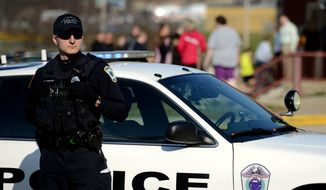 A police officer guards the entrance Heritage Elementary School as students are dismissed after more than a dozen students were stabbed by a knife wielding suspect at nearby Franklin Regional High School on Wednesday, April 9, 2014, in Murrysville, Pa., near Pittsburgh. The suspect, a male student, was taken into custody and is being questioned. (AP Photo/Tribune Review, Sean Stipp)  PITTSBURGH OUT