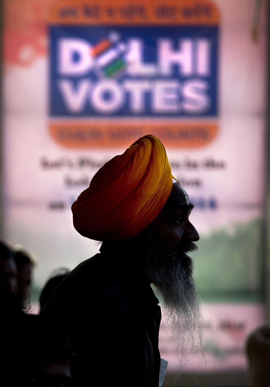 An Indian Sikh stands next to an Indian Election Commission banner urging people to vote, at a bus stop in New Delhi, India, Wednesday, April 9, 2014. India started the world's largest election Monday where the country's 814 million electorate will vote in stages over the next five weeks. (AP Photo/Manish Swarup)