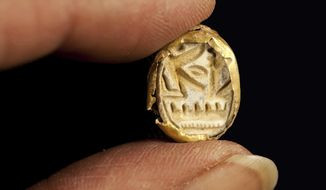 This undated photo released by Israel's Antiquities Authority shows a scarab seal ring encased in gold, carved with the name of Pharaoh Seti I, who ruled ancient Egypt in the 13th century BC, found at Tel Shadud, an archaeological mound in the Jezreel Valley. Israeli archaeologists have unearthed a rare sarcophagus featuring a slender face and a scarab ring inscribed with the name of an Egyptian pharaoh, Israel's Antiquities Authority said Wednesday April 9, 2014. (AP Photo/Israel's Antiquities Authority)