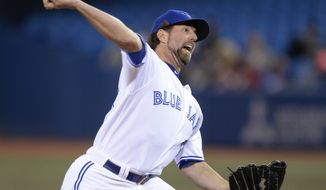 Toronto Blue Jays starting pitcher R.A. Dickey throws to a Houston Astros batter during the first inning of baseball game in Toronto on Thursday, April 10, 2014. (AP Photo/The Canadian Press, Frank Gunn)