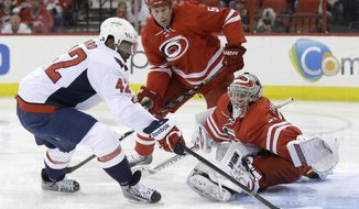 Washington Capitals' Joel Ward (42) shoots against Carolina Hurricanes goalie Anton Khudobin (31), of Kazakhstan, during the first period of an NHL hockey game in Raleigh, N.C., Thursday, April 10, 2014. Ward scored on the play. Hurricanes' Mike Komisarek (5) watches the play. (AP Photo/Gerry Broome)