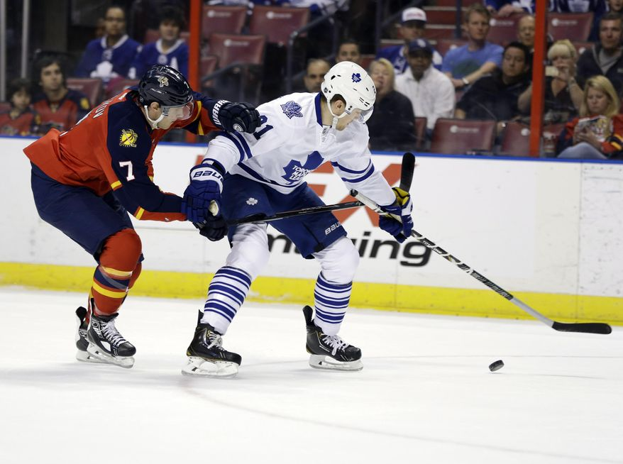 Florida Panthers defenseman Dmitry Kulikov (7) and Toronto Maple Leafs left wing James van Riemsdyk (21) chase the puck in the first period of an NHL hockey game on Thursday, April 10, 2014, in Sunrise, Fla. (AP Photo/Lynne Sladky)