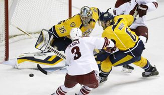 Nashville Predators goalie Pekka Rinne (35), of Finland, blocks a shot by Phoenix Coyotes defenseman Keith Yandle (3) in the third period of an NHL hockey game on Thursday, April 10, 2014, in Nashville, Tenn. Predators' Shea Weber (6). Phoenix Coyotes right wing Shane Doan (19)  also defend. The Predators won 2-0. (AP Photo/Mark Humphrey)