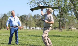 In this photo taken on April 8, 2014, Tim Miller, left, EquuSearch founder, and volunteer Gene Robinson, who builds the group's drones, launch a drone in Santa Fe, Texas. The group relies mostly on horseback and all-terrain vehicles to search rough terrain. But it also employs 4-pound aerial drones to survey the ground with digital cameras. (AP Photo/Houston Chronicle, Mayra Beltran) MANDATORY CREDIT