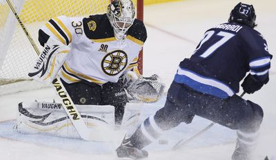 Boston Bruins goaltender Chad Johnson (30) saves a shot by Winnipeg Jets' Eric Tangradi (27) during the first period of an NHL hockey game Thursday, April 10, 2014, in Winnipeg, Manitoba. (AP Photo/The Canadian Press, John Woods)