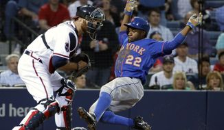 New York Mets' Eric Young Jr., right, slides into home plate to beat the throw to Atlanta Braves catcher Ryan Doumit to score off a single by teammate David Wright in the third inning of a baseball game, Thursday, April 10, 2014, in Atlanta. (AP Photo/David Goldman)