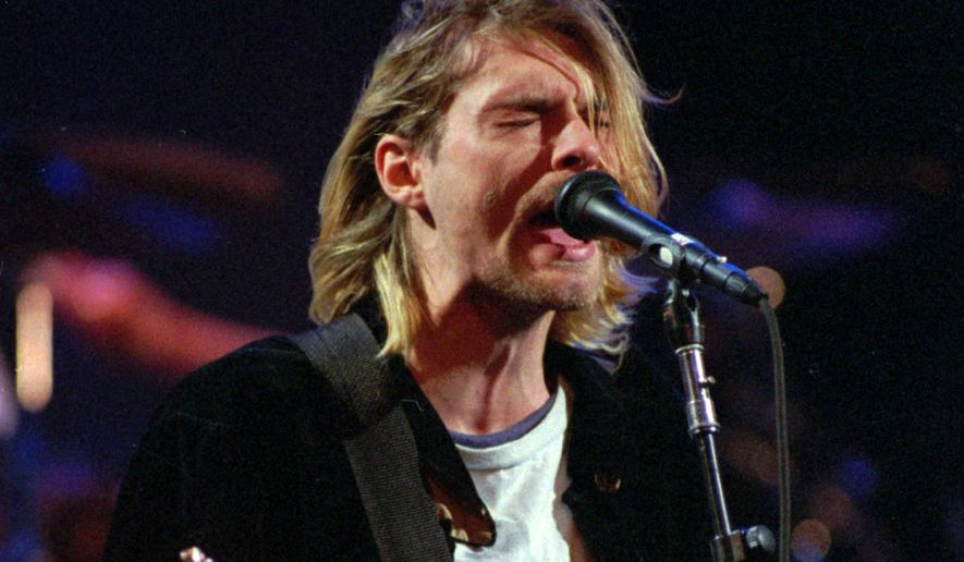 This Dec. 13, 1993 file photo shows Kurt Cobain of the Seattle band Nirvana performing in Seattle, Wash. (AP Photo/Robert Sorbo, File)