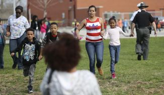 Students and parents are reunited after a lockdown in response to a shooting in the parking lot of Liberty Elementary. The lock down happened just minutes before the students there were to be dismissed, Thursday, April 10, 2014 in Columbus, Ohio. (AP Photo/Columbus Dispatch, Courtney Hergesheimer)
