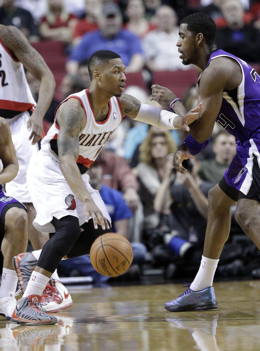 Portland Trail Blazers guard Damian Lillard, left, drives against Sacramento Kings forward Jason Thompson during the first half of an NBA basketball game in Portland, Ore., Wednesday, April 9, 2014. (AP Photo/Don Ryan)