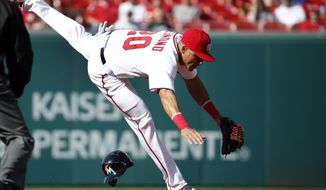 Washington Nationals shortstop Ian Desmond tries to keep his balance after missing the tag at second base as Miami Marlins Christian Yelich steals the base during the first inning of a baseball game at Nationals Park, Thursday, April 10, 2014, in Washington. (AP Photo/Alex Brandon)