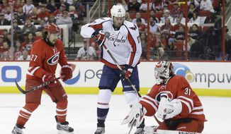 Washington Capitals' Dustin Penner (17) tries to score against Carolina Hurricanes goalie Anton Khudobin (31), of Kazakhstan, as Hurricanes' Justin Faulk (27) defends during the first period of an NHL hockey game in Raleigh, N.C., Thursday, April 10, 2014. (AP Photo/Gerry Broome)