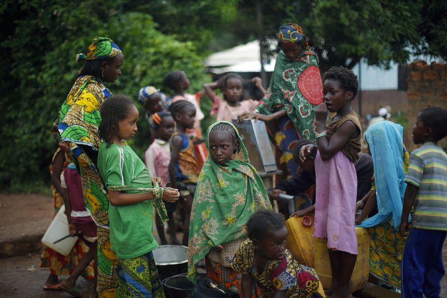 Muslim children gather at a water pump outside the mosque at PK12 in Bangui, Central African Republic, Thursday, April 10, 2014. A few hundred Muslims remain at the entrance of Bangui, waiting for transport to neighboring Chad. (AP Photo/Jerome Delay)