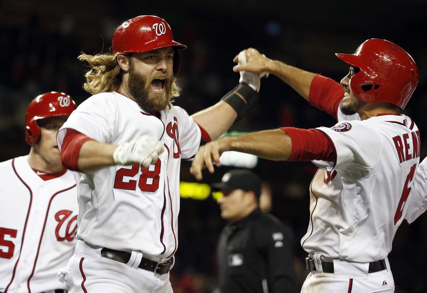 Washington Nationals' Jayson Werth, center, celebrates his game winning grand slam with Anthony Rendon, right, and Nate McLouth, during the eighth inning of a baseball game against the Miami Marlins at Nationals Park Wednesday, April 9, 2014, in Washington. The Nationals won 10-7. (AP Photo/Alex Brandon)