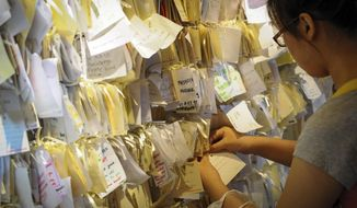 ** FILE ** A woman ties a message card for passengers onboard the missing Malaysia Airlines Flight 370 at a shopping mall in Petaling Jaya, near Kuala Lumpur, Malaysia, Thursday, April 10, 2014. (AP Photo)