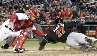 Washington Nationals catcher Jose Lobaton (59) tags out Miami Marlins' Giancarlo Stanton (27) at home, as umpire Dan Bellino watches, during the eighth inning of a baseball game at Nationals Park Wednesday, April 9, 2014, in Washington. The Nationals won 10-7. (AP Photo/Alex Brandon)