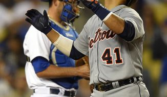 Detroit Tigers' Victor Martinez, right, looks to the sky after hitting a solo home run as Los Angeles Dodgers catcher Drew Butera looks on during the 10th inning of a baseball game, Wednesday, April 9, 2014, in Los Angeles. (AP Photo/Mark J. Terrill)