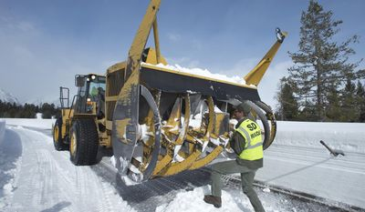 Adam Mates rotates the plow's huge rotor during a stop to replace a shear bolt on the mechanism Friday, April 4, 2014 in Moose, Wy. Mates is one of a crew of 13 whose job it is to clear the roads in Grand Teton National Park each spring. (AP Photo/Jackson Hole News & Guide, Bradly J. Boner)