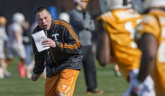 FILE - In this March 8, 2014 file photo, Tennessee head coach Butch Jones yells to his squad during spring practice in Knoxville, Tenn. Tennessee's Orange & White Game on Saturday, April 12, 2014, won't end the Volunteers' quarterback competition, but it should put the four-way battle into clearer focus.  (AP Photo/The Knoxville News Sentinel, Paul Efird, File)
