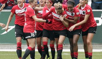 FILE - In this April 21, 2013, file photo, the Portland Thorns celebrate after Kathryn Williamson, third from right, scores during the first half of a National Women's Soccer League soccer game against the Seattle Reign in Portland, Ore. The defending NWSL champion Thorns will open the season Saturday, April 12, 2014, against the expansion Houston Dash in Houston. (AP Photo/Don Ryan, File)