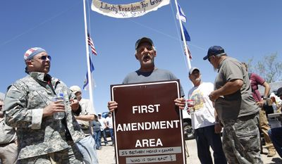"Charlie Brown holds up a sign from the Bureau of Land Management's ""first amendment area"" during a protest of the Bureau of Land Management's roundup of cattle near Bunkerville, Nev. Thursday, April 10, 2014. The Bureau of Land Management removed their two ""first amendment areas"" from the area.(AP Photo/Las Vegas Review-Journal, John Locher)"