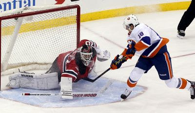 New York Islanders' Ryan Strome (18) scores a goal on New Jersey Devils goalie Martin Brodeur (30) to give the Islanders a 3-2 shootout victory in an NHL hockey game on Friday, April 11, 2014, in Newark, N.J. (AP Photo/Julio Cortez)