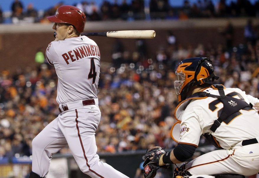 Arizona Diamondbacks' Cliff Pennington, left, drives in two runs with a bases-loaded single against the San Francisco Giants during the second inning of a baseball game on Thursday, April 10, 2014, in San Francisco. (AP Photo/Marcio Jose Sanchez)