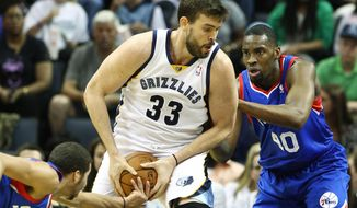 Philadelphia 76ers guard Michael Carter-Williams, left, tries to steal the ball from Memphis Grizzlies center Marc Gasol (33) who drives against 76ers forward Jarvis Varnado (40) in the first half of an NBA basketball game on Friday, April 11, 2014, in Memphis, Tenn. (AP Photo/Mike Brown)