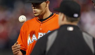 Miami Marlins' Jose Fernandez tosses the ball as he waits for manager Ryne Sandberg, right, to take him out during the fifth inning of a baseball game against the Philadelphia Phillies, Friday, April 11, 2014, in Philadelphia. (AP Photo/Tom Mihalek)