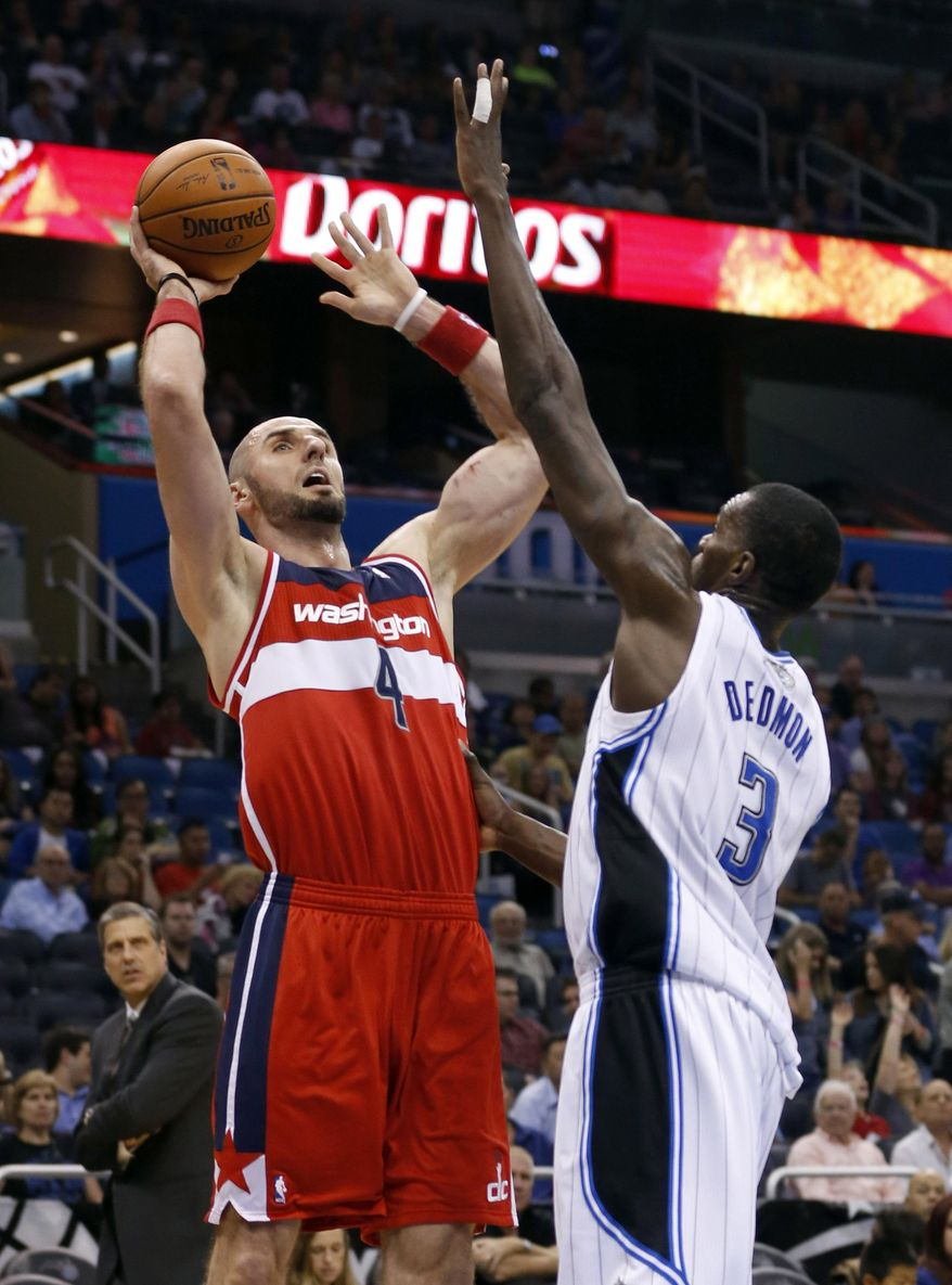 Washington Wizards center Marcin Gortat (4), of Poland, shoots over Orlando Magic center Dewayne Dedmon (3) during the first half of an NBA basketball game in Orlando, Fla., Friday, April 11, 2014. (AP Photo/Reinhold Matay)