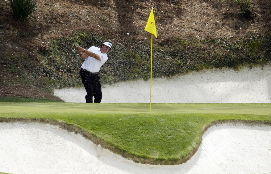 Phil Mickelson hits out of a bunker on the 12th hole during the second round of the Masters golf tournament Friday, April 11, 2014, in Augusta, Ga. (AP Photo/Charlie Riedel)