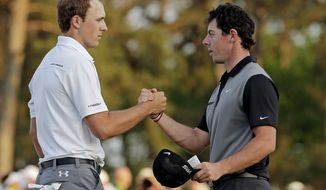 Jordan Spieth, left, shakes hands with Rory McIlroy, of Northern Ireland, on the 18th green following their second round of the Masters golf tournament Friday, April 11, 2014, in Augusta, Ga. (AP Photo/Charlie Riedel)