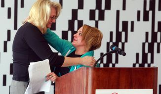 "Lorrie Wnuk, left, victim services coordinator for the Natrona County Sheriff's Department, hugs Sarah Kostovny on Monday, April 7, 2014 at Casper College in Casper, Wyo. Kostovny, a former Casper resident who was the victim of ""Craigslist rapist"" Ty Oliver McDowell in 2009, told her story during an event recognizing National Crime Victims' Rights Week. (AP Photo/Casper Star-Tribune, Alan Rogers)"