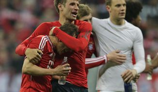 Bayern's Philipp Lahm, left, Thomas Mueller, centre, and Bayern goalkeeper Manuel Neuer celebrate at the end of the Champions League quarterfinal second leg soccer match between Bayern Munich and Manchester United in the Allianz Arena in Munich, Germany, Wednesday, April 9, 2014. Bayern won 3-1 to win the tie 4-2 on aggregate.    (AP Photo/Matthias Schrader)